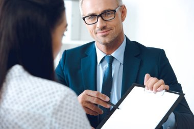 insurance agent pointing at clipboard in clients hand at tabletop in office