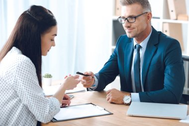 smiling insurance agent giving pen to female client for signing papers at tabletop in office