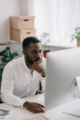 zamyšlený pohledný americký podnikatel pracuje u počítače v kanceláři