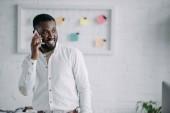Veselá hezký americký podnikatel mluví o smartphone v kanceláři a hledat dál