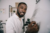 Fotografie smiling handsome african american businessman drawing on flipchart in office and  looking at camera