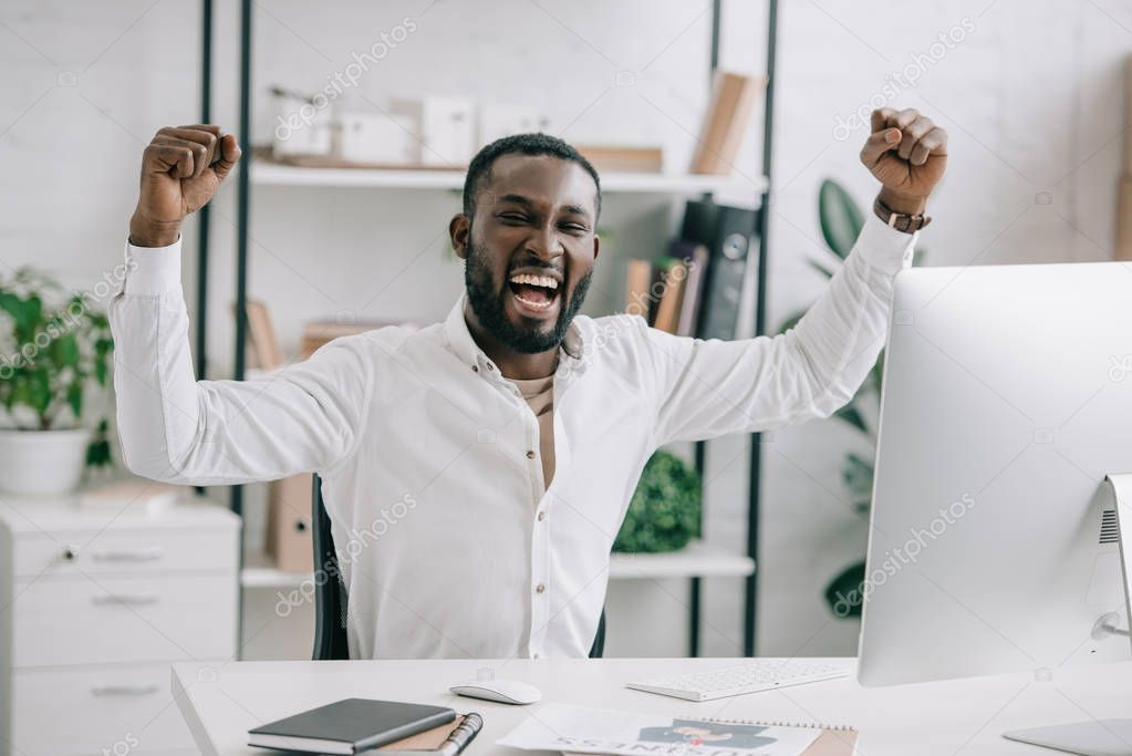 Excited african american businessman screaming and showing yes gesture in office. Man celebrate win a bet with a gambling, soccer bet, sports gambling