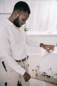 Fotografie boční pohled na krásný africký americký architekt pracuje na modelu architektury v úřadu