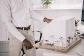 Fotografia immagine potata di afro-americano architetto lavorando su modello di architettura in ufficio