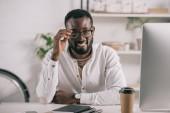 usmívající se pohledný americký podnikatel dojemné brýle v úřadu
