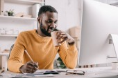 Fotografie handsome african american designer in orange sweater drinking coffee and drawing in notebook in office