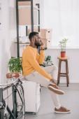 Fotografia designer americano africano in maglione giallo ne su smartphone in ufficio moderno con moto