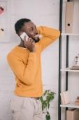 Fotografia progettazione afroamericano allegro in maglione giallo ne su smartphone in ufficio moderno