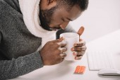 tired diseased african american man with cup of hot drink and pills sitting at workplace