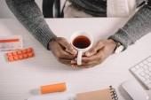 Fotografia ritagliate la vista delluomo malato con la tazza di tè caldo e farmaci che si siede al posto di lavoro