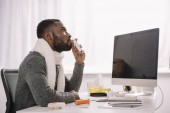 Fotografie ill african american businessman in warm scarf with nose spray at workplace with computer
