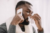 diseased african american man with runny nose holding napkin while talking on smartphone