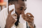 ill african american man with runny nose holding napkin while talking on smartphone