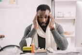 nemocný americký muž s hlavy sedí na pracovišti s léky