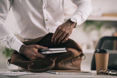 cropped image of african american businessman putting notebooks into briefcase in office