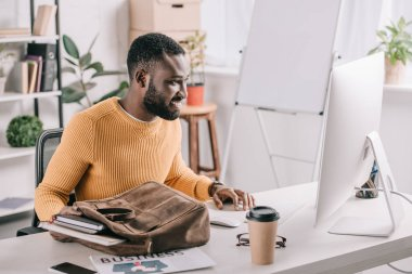 Handsome african american designer in orange sweater taking notebooks from briefcase and looking at computer in office stock vector