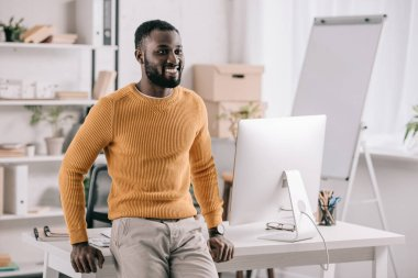 cheerful handsome african american designer in orange sweater leaning on table and looking away in office