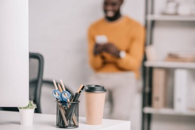 Selective focus of computer, coffee to go and office supplies on workplace and designer standing in modern office stock vector