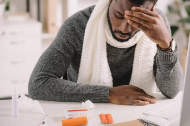 Tired african american man with headache looking at pills while sitting in office stock vector