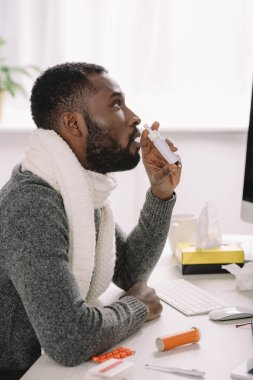 diseased african american businessman in warm scarf with nose spray at workspace
