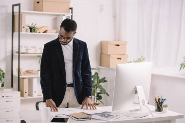 professional african american architect working with blueprint in office with computer