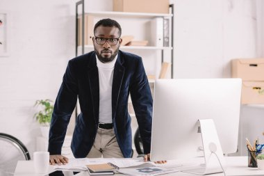 Handsome african american architect working with blueprint at workspace with computer stock vector