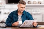 usmívající se muž v kostkované košili držící šálek kávy a čtení noviny doma