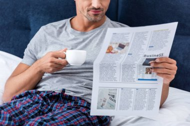 Cropped image of businessman with cup of coffee reading business newspaper in bed at home stock vector