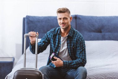 happy male traveler sitting on bed with smartphone and flight ticket near wheeled bag at home