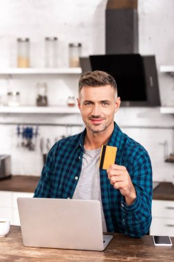 Handsome man holding credit card and smiling at camera while using laptop at home stock vector