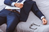 cropped shot of businessman in suit holding laptop and lying on bed