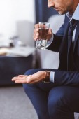 cropped shot of businessman in suit holding glass of water and pills at home
