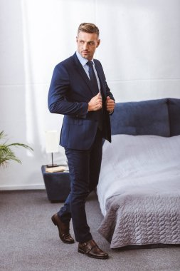 full length view of handsome adult man wearing suit jacket and looking away in bedroom