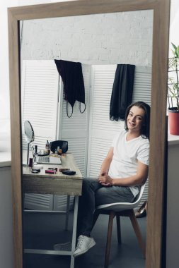 view through mirror reflection young transgender man looking at camera at home