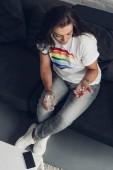 Fotografie pohled z vysoké úhlu depresi mladých transgender člověka s prášky a sklenicí vody sedí na gauči