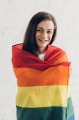 boldog transznemű férfi büszkeség zászló és a kamera előtt fehér téglafal nézett