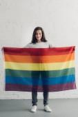 Fotografie transgender šťastný muž, který držel pride vlajka před bílou cihlová zeď