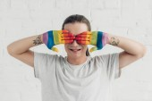 Fotografie usmívající se muž transgender pokrývající oči rukama malované v barvách vlajky hrdosti přední bílá cihlová zeď