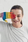 Fotografie usmívající se muž transgender pokrývající oko s ručně malované v barvách vlajky hrdosti přední bílá cihlová zeď