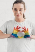 smiling young transgender man making heart sign with hands in colors of pride flag in front of white brick wall