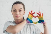 young transgender man making heart sign with hands in colors of pride flag in front of white brick wall