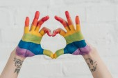 cropped shot of hands painted in colors of pride flag showing heart gesture in front of white brick wall