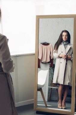young transgender man in trench coat looking at mirror at home