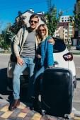 coppia di turisti sorridenti con bagagli vicino automobile sulla via
