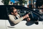 Fotografie mladý muž vyklání z okna auta jízdy automobilu