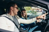 Fotografie side view of man pointing way to girlfriend on drivers seat in car