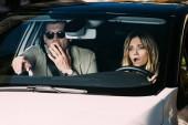 Šokovaný muž ukazující cestu k přítelkyni to řidičské auto