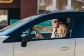 boční pohled na usmívající se žena, která řídila auto s přítelem poblíž, cestování koncept
