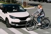 Fotografie žena jedoucí na kole při křížení silnice s ovladačem v autě