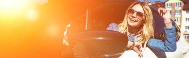neşeli genç kadın sokakta arabadan eğilerek güneş gözlüğü